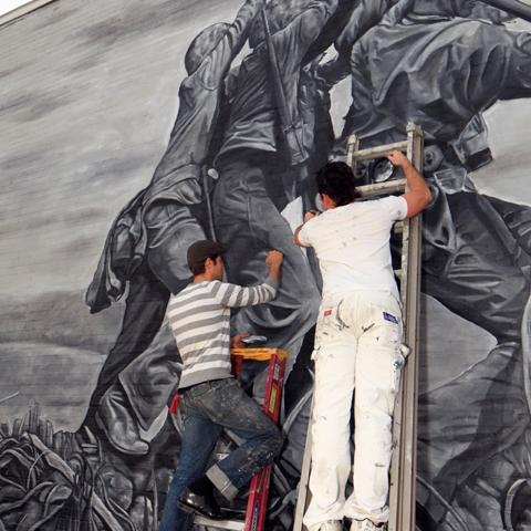 Mike Sekletar, left, and Ryan Shannon painting a mural in downtown Amherst, Ohio based on the famous photo of the U.S. flag-raising on Iwo Jima during World War II.